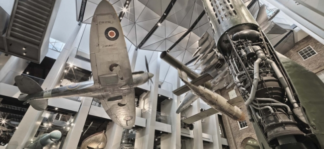 Photo: Atrium of the IWM London, the exhibits include a Supermarine Spitfire, a V-1 flying bomb, a V-2 rocket, a Harrier Jump Jet, by Imperial War Museums (IWM)
